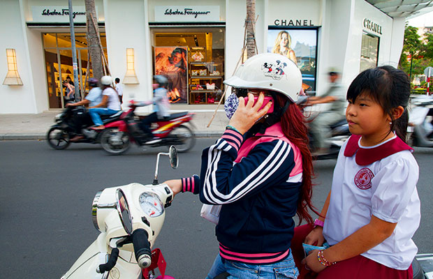 A mother and her daughter ride on a scooter in front of a brand new luxury shopping centre in Ho Chi Minh City, Vietnam