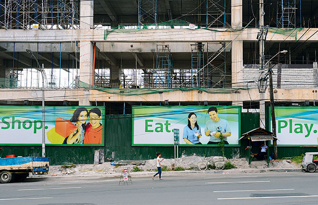 A pedestrian walks past an advertisement for a shopping mall under construction in Manila