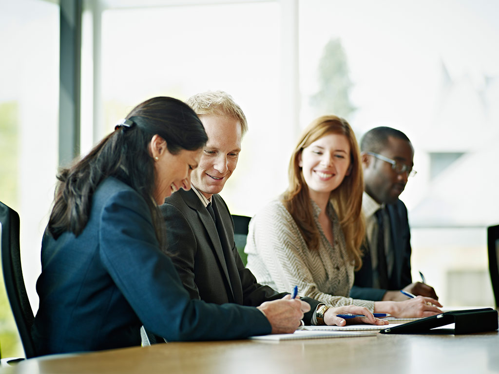 Men and women discuss meeting notes in boardroom