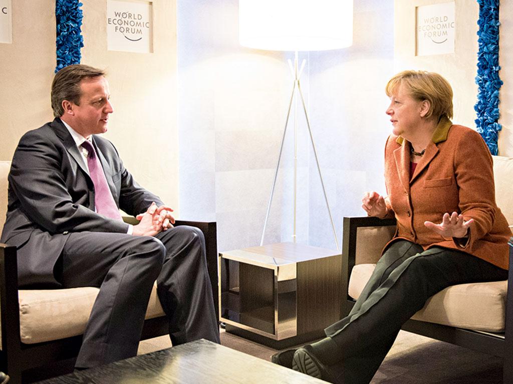 UK Prime Minister David Cameron and German Chancellor Angela Merkel talk between events at the 2013 meeting