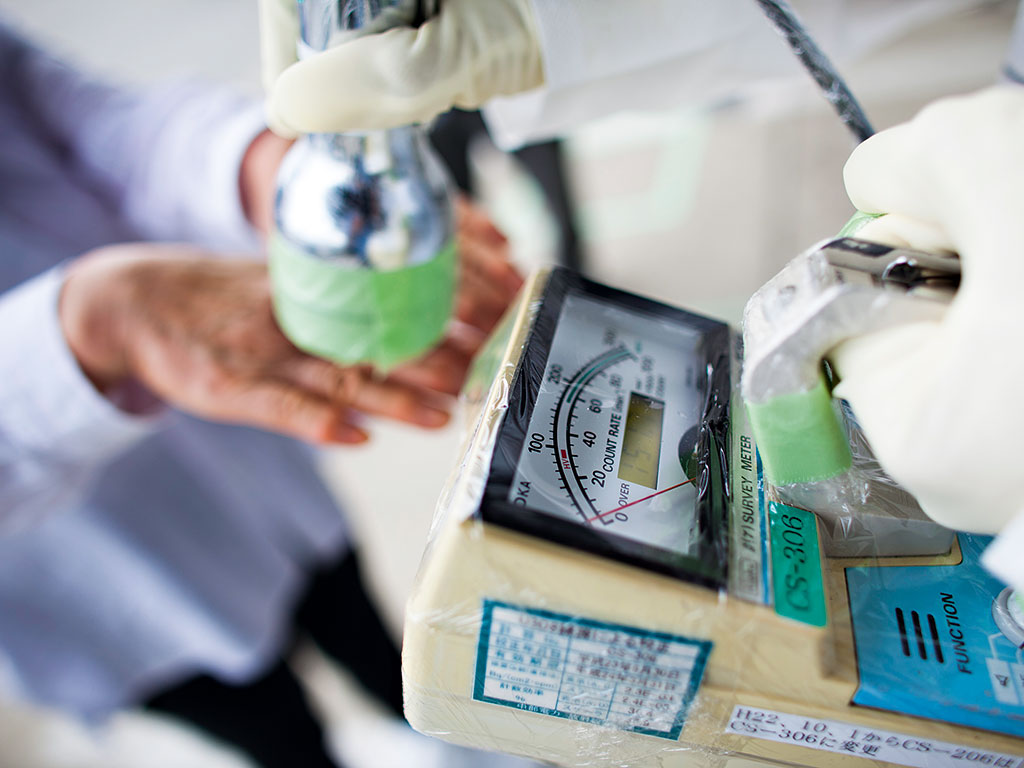Workers measure radiation within the Fukushima exclusion zone