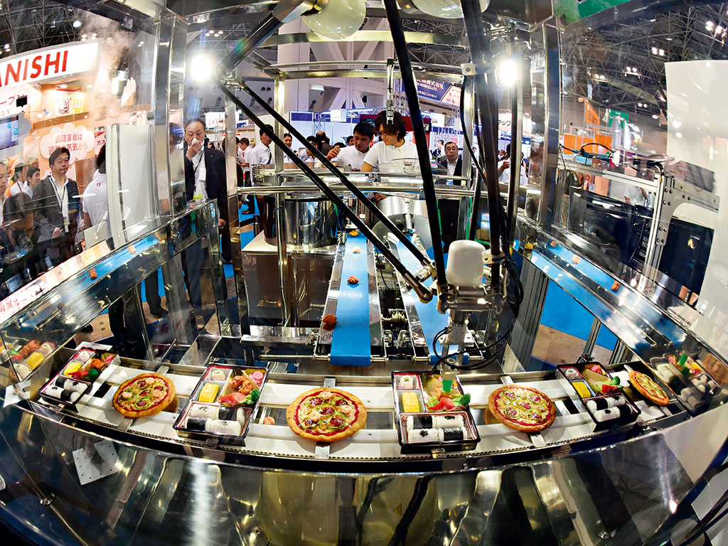 Kawasaki Heavy Industries uses robot machinery to pack lunches and make pizzas